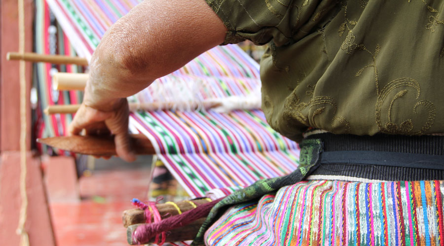 a backstrap weaver pushes the weft yarn securely into place