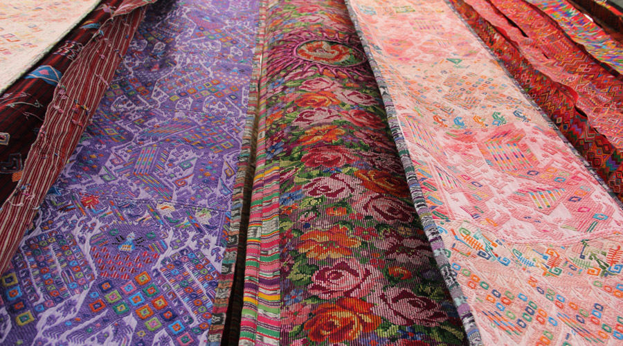 Meridian | Huipil embroidery in the form of long sash style garments hang in the market at Chichicastenago