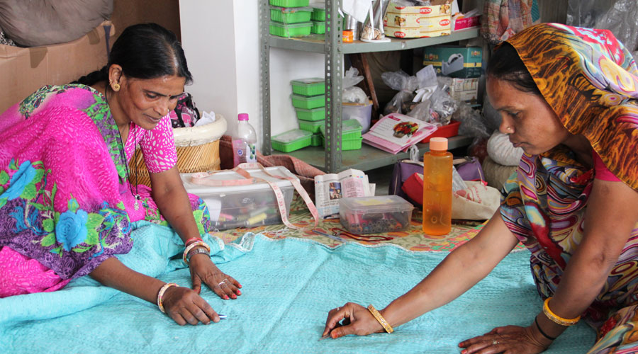 Meridian | These women are completing the finishing touches on to a hand-stitched kantha blanket.
