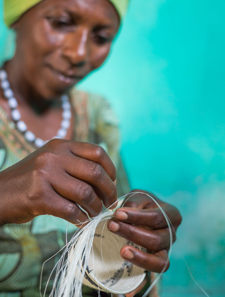 Meridian | A member of our artisan partner's cooperative in Rwanda demonstrates the detailed process she uses to create a small basket.