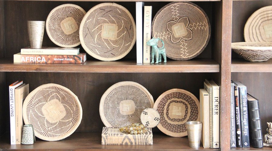 Meridian | A Bookshelf featuring Woven Palm Baskets, Recycled Glass Bead Strands, and other global finds.