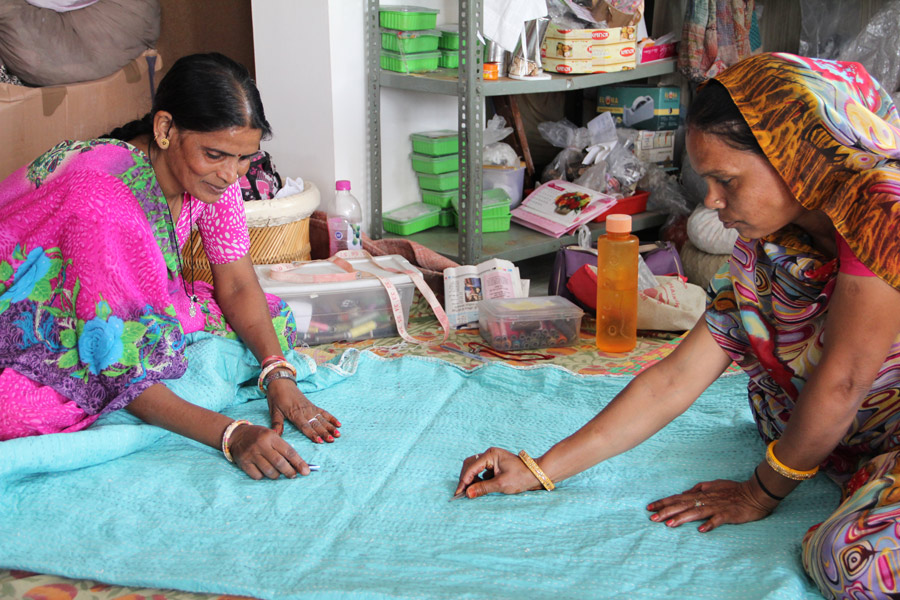 Two artisan women perform quality assessment and finishing touches in our partner's textile workshop in Rajasthan, India. | Meridian