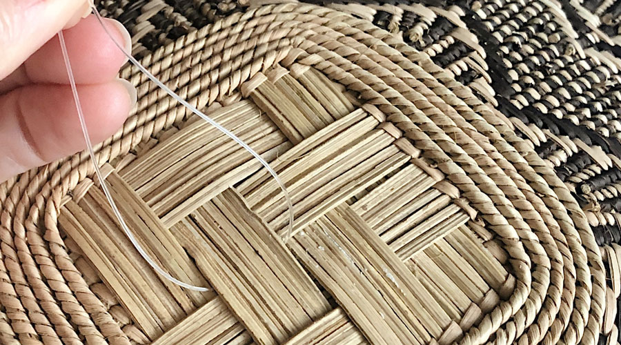 Four Easy Steps to Hang a Basket Wall - Thread the fishing line through the open weaves of the front of the basket, so that the open ends of your loop are on the back. | Meridian