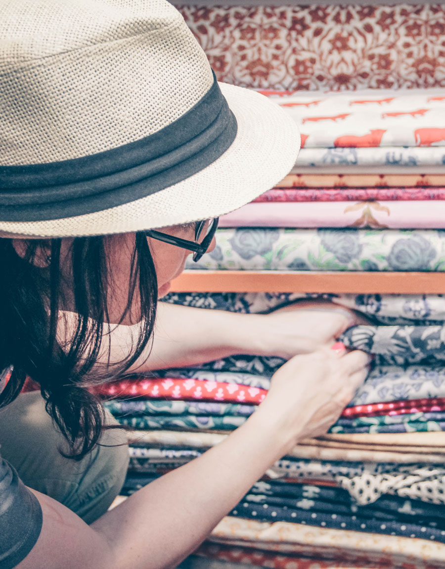 Meridian Founder Ashley Viola digs into a large pile of block print textiles in Jaipur, India.