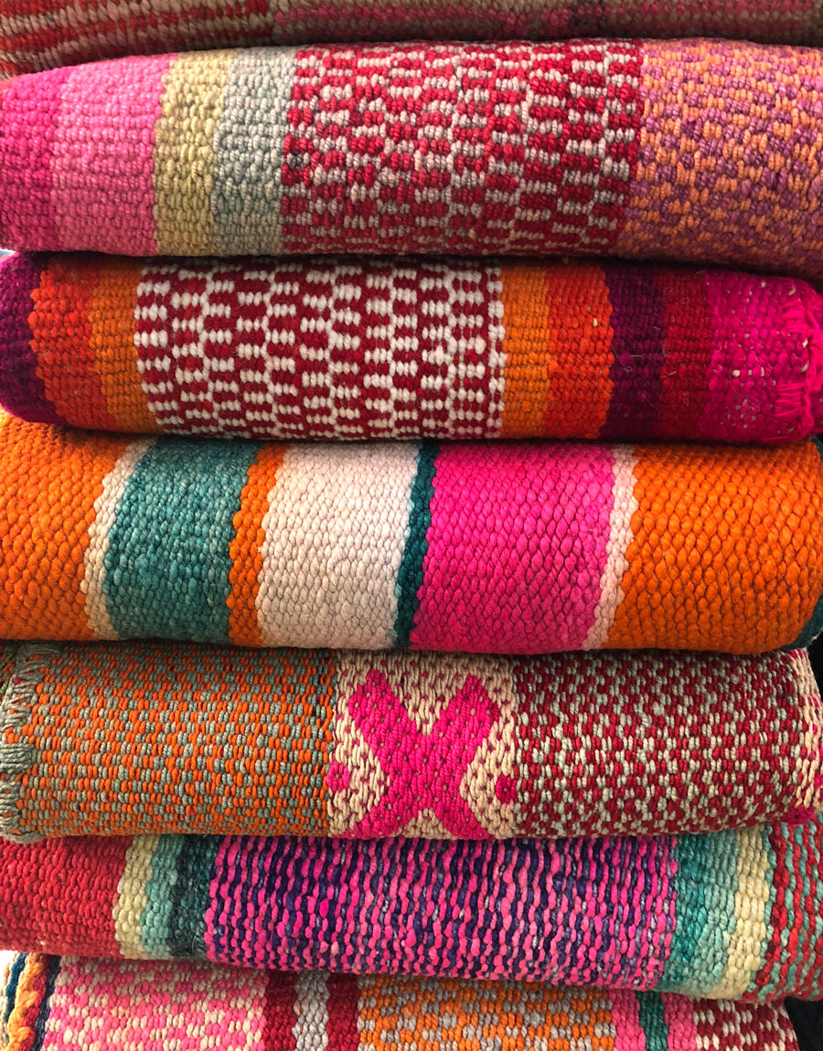 Meridian | A stack of colorful handwoven frazada blankets from Peru.