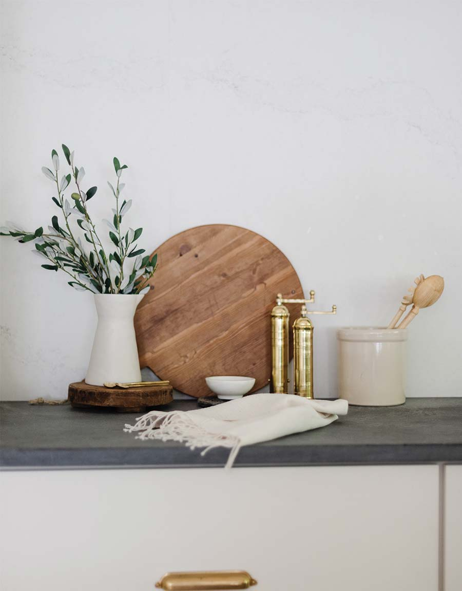 eucalyptus coming out of the white carafe - featuring a Vintage Chapati Board Riser - fall home decor